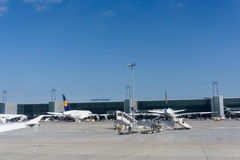 Lufthansa planes and airport equipment parked outside terminal i. Frankfurt Germany - August 15, 2016: Lufthansa planes and airport equipment parked outside Stock Photo