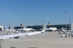 Lufthansa planes and airport equipment parked outside terminal i. Frankfurt Germany - August 15, 2016: Lufthansa planes and airport equipment parked outside Royalty Free Stock Images