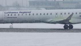 Lufthansa Regional plane taxiing in heavy snow, low visibility. Lufthansa Regional jet taxiing in Munich Airport, Germany, winter time with snow on runway stock footage