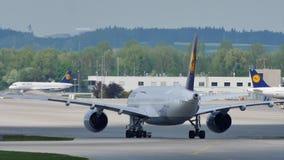 Lufthansa spiana facendo il taxi sulla pista nell'aeroporto di Monaco di Baviera, MUC stock footage