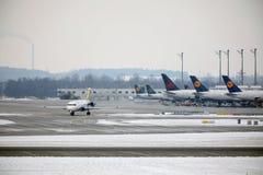 Lufthansa surface aux portes terminales, l'aéroport de Munich, horaire d'hiver avec la neige Photographie stock libre de droits
