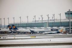 Lufthansa surface aux portes terminales, l'aéroport de Munich, horaire d'hiver avec la neige Photos stock