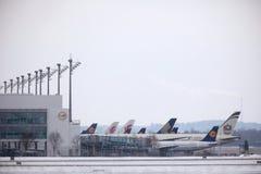 Lufthansa surface aux portes terminales, l'aéroport de Munich, horaire d'hiver avec la neige Photos libres de droits