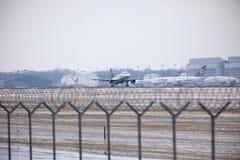 Lufthansa surfacent l'atterrissage dans l'aéroport de Munich, horaire d'hiver avec la neige Photographie stock