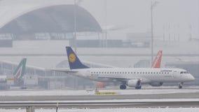 Lufthansa y EasyJet que llevan en taxi en las nevadas fuertes, aeropuerto de Munich, MUC metrajes