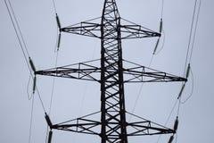 Lufthochspannungsfernleitungen der elektrischen Energie Obenliegende Linien legen Strom über Boden durch die Drähte, die zu befes stockfoto