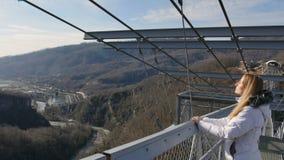 Luftiger Fußgängerbrückenbau über Abgrund, skybridge Aussichtsplattform Enjoing Sonnenlicht- und Landschaftsansicht der Frau stock footage