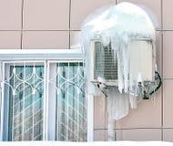 Luftkonditioneringsapparat som täckas med djupfryst is och istappar nära fönster Royaltyfria Foton