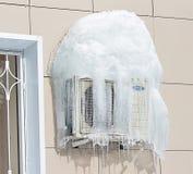 Luftkonditioneringsapparat som täckas med djupfryst is och istappar nära fönster Arkivbild