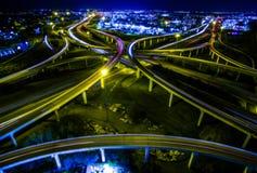 Luftlandstraßen-Austausch-Schleifen und Drehung arounds als die Stadtlichter wachsen mit Nachtlichtgeschwindigkeit anzieht auf ei stockfotos