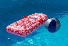 Luftmadrass- och vattenboll i simbassäng Arkivbilder