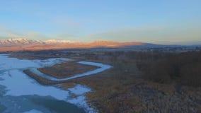 Luftpanoramablick von einem gefrorenen See und dann von Waldung von Bäumen mit Bauernhöfen, Felder und mountians im Abstand stock video footage