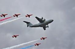 Luftparade von RAF Red Arrows einen Airbus A400M eskortierend Lizenzfreie Stockfotografie