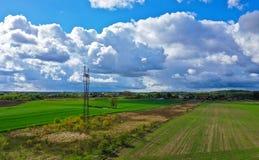 Luftperspektivenansicht über ländliche Landschaft mit Haus, Wald, Wolken, Feldern und Starkstromleitungsturm lizenzfreie stockfotos