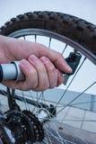 Luftpump på cykelgummihjulet vid handen arkivfoton