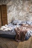 Luftsängen med grå sänglinne och en brun räkning på träkostnader för ett golv mot bakgrunden av en mäktig vägg inomhus royaltyfri bild
