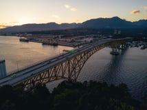 Luftschuß der Brücke über Fluss während Sonnenuntergang hinter Bergen lizenzfreies stockbild