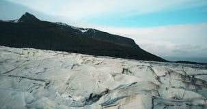 Luftschuß der Eisspalte mit schwarzer vulkanischer Asche Hubschrauber, der über den großen Gletscher Vatnajokull in Island fliegt stock footage