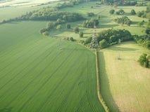 Luftschuß der Felder mit Starkstromleitungen Stockfotografie