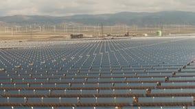 Luftschuß der niedrigen Höhe des Sonnenkraftwerks und der entfernten Windkraftanlagen stock footage