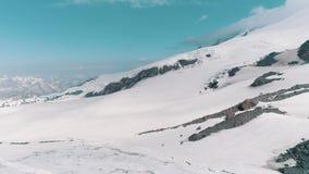Luftschuß des Gebirgsabhangs bedeckt im Schnee und in den Bahnen stock video footage
