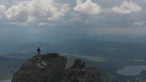 Luftschuß des Schattenbildes eines Mannes, der zur Spitze des Berges klettert stock video footage