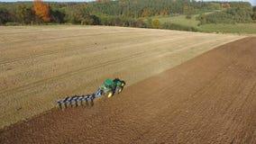 Luftschuß des Traktors schwarzen Boden nah an Waldherbstsonnenuntergang pflügend stock video