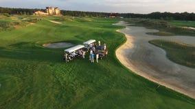 Luftschuß einer Gruppe von Personen, die sich in den Golfmobilen auf einem Golfplatz hinsetzt stock footage