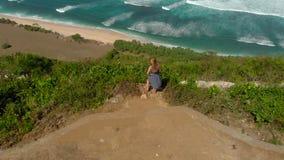 Luftschuß einer jungen Frau, die einen Fernstrand - nyang nyang- auf der Bali-Insel besucht Stellung auf einem Felsen, der betrac stock footage