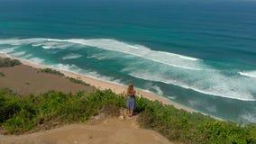 Luftschuß einer jungen Frau, die einen Fernstrand - nyang nyang- auf der Bali-Insel besucht Stellung auf einem Felsen, der betrac stock video footage