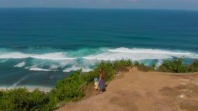 Luftschuß einer jungen Frau und ihres Sohns, die einen Fernstrand - nyang nyang- auf der Bali-Insel besuchen Stellung auf einem F stock video footage