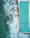 Luftschuß eines großen Swimmingpools auf dem Ufer mit Felsen und des Wassers nahe bei dem Strand stockfoto
