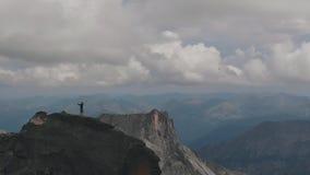 Luftschuß eines Mannes, der auf einen Berg steht Junger Bergsteiger hebt glücklich seine Hände an, nachdem er den Berg geklettert stock video footage