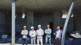 Luftschuß von den Erbauern team auf Baustelle Plan des Projektes mit der Architekten- und Auftragnehmeranwendung besprechend stock footage