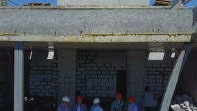 Luftschuß von den Erbauern team auf Baustelle Plan des Projektes mit der Architekten- und Auftragnehmeranwendung besprechend stock video footage
