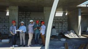 Luftschuß von den Erbauern team auf Baustelle Plan des Projektes mit der Architekten- und Auftragnehmeranwendung besprechend stock video