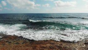 Luftschuß von den Meereswogen, die gegen felsige Klippen spritzen, setzen auf den Strand Stürmische Meereswellen felsigen Strand  stock video