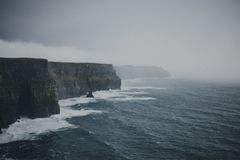 Luftschuß von den Spritzenwellen, die den felsigen Strand an einem nebeligen Tag schlagen stockbild
