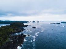 Luftschuß von den Wellen, die Felsen auf Ozeanküste schlagen Lizenzfreie Stockfotos