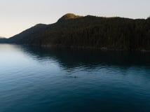 Luftschuß von Kayaker auf See mit Bergen während Sonnenuntergang lizenzfreie stockbilder