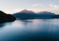 Luftschuß von Kayaker auf See mit Bergen während Sonnenuntergang lizenzfreies stockfoto