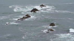 Luftschuß von Meereswogen und von Klippe - Wellen, die oben auf einem Felsen im Meer sich waschen stock footage