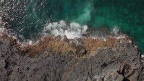 Luftschuß Aufriss unten Das Blau und des Türkisschäumendes Wasser Ozeans und -meeres und die vulkanische Küstenlinie von stock video