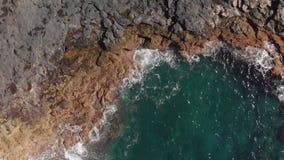 Luftschuß Aufriss unten Die Wellen spritzen Blau und Türkis in der Farbe und die vulkanische Küstenlinie von stock video footage
