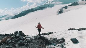 Luftschussfrauentanzen auf Felsen an der schneebedeckte Gebirgsmalerischen Landschaft stock footage