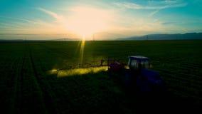 Luftsonnenaufgangansicht des Landwirtschaftstraktors pflügend und auf Feld sprühend stock video footage