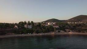 Luftszene des Trikorfo-Strandufers mit Häuschen und grünen Hügeln, Griechenland stock video