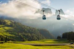 Lufttram-Drahtseilbahn, die, während des Sonnenuntergangs, mit grünem Gras steigt lizenzfreies stockbild