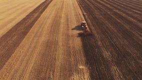 Lufttrieb ein gelber Traktor, der den Boden pflügt stock video
