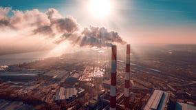 Luftverschmutzung durch den Rauch, der aus zwei Fabrikkamine herauskommt Schattenbild des kauernden Geschäftsmannes Lizenzfreie Stockfotografie